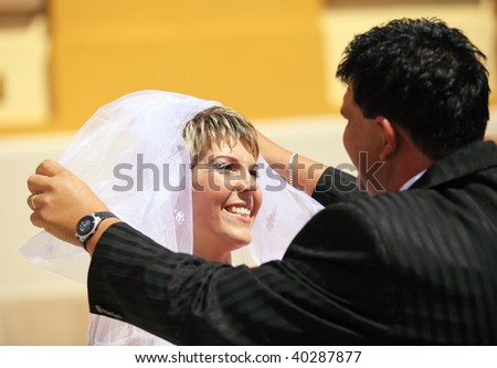 Groom lifting bride's veil outdoor