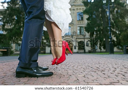 Groom lifting his bride up during their walk, close-up of lower part of the bodies - stock photo