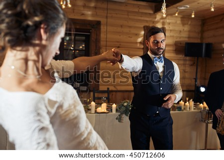 Groom looks at a bride reaching his hand to her during a dance