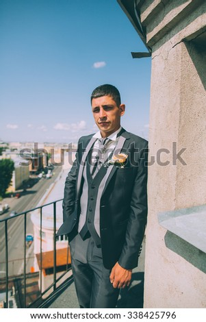 Groom on the roof of the city in a suit with a plastron and buttonhole