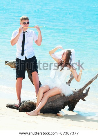 Groom playing a flute for his bride - stock photo