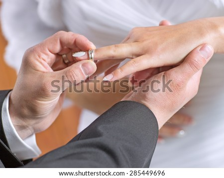 Groom puts a wedding ring on finger of his lovely bride - stock photo