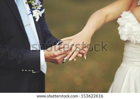 groom puts a wedding ring on finger of his lovely bride, Wedding couple holding hands on garden background - stock photo