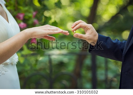 groom puts on the ring on the finger of the bride - stock photo