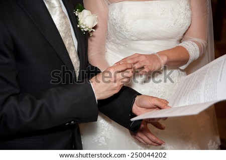 Groom puts ring on the Bride's hand  - stock photo