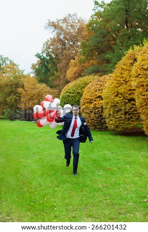 Groom running through the grass.Happy groom.Portrait of a handsome groom in a blue suit and white shirt  - stock photo
