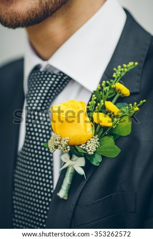 groom's hand arranging yellow boutonniere flower on suit - stock photo
