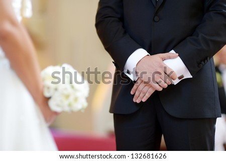 Groom's hands during the wedding ceremony in church