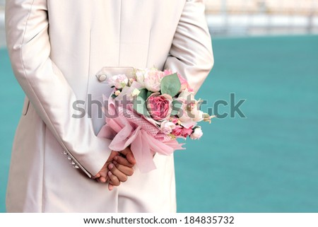 Groom's hands holding wedding bouquet