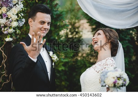 Groom shows a wedding ring on his hand to the guests while bride laughs behind him
