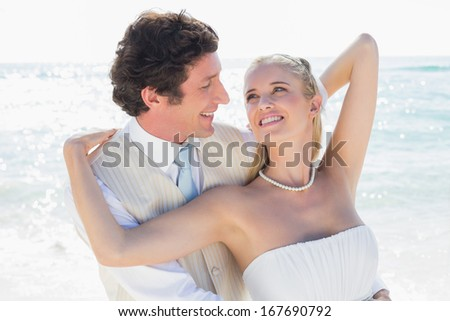 Groom smiling at and embracing his bride at the beach