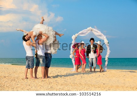 Groom standing with bridesmaids under archway on beach and waiting for his drunk bride - stock photo