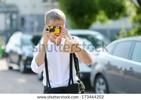 Groom taking a photo of his bride with a instant camera - stock photo