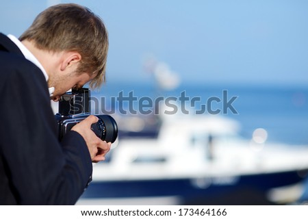 Groom taking a photo of his bride with a vintage camera - stock photo
