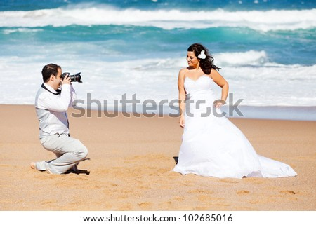 groom taking bride's photos on beach - stock photo