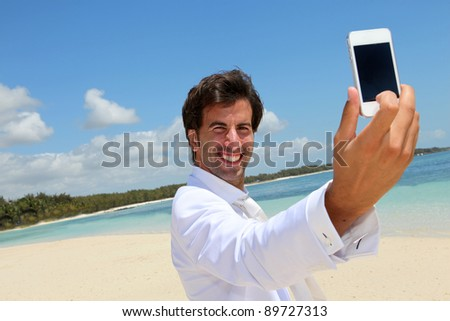 Groom taking picture of himself on a beach - stock photo