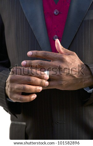Groom trying on his wedding band - stock photo