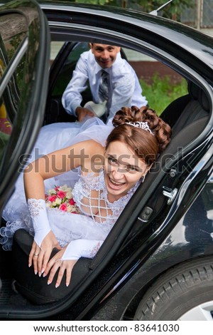 Groom trying to drag the bride out of the car. Having fun.