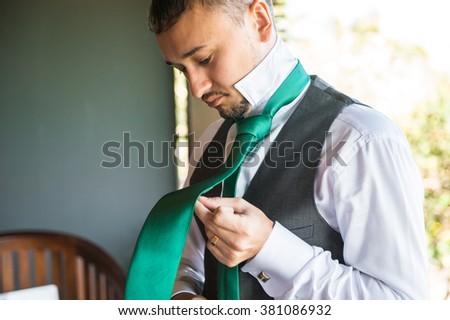 Groom tying tie - stock photo