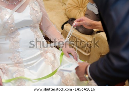 groom untying ribbons on bride's hand