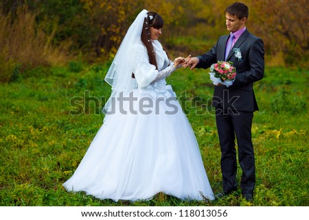 groom wears ring bride newlyweds standing on green grass in autumn in forest
