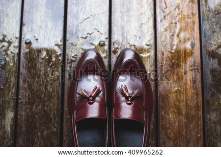 Groom wedding details. Leather shoes on wooden background with raindrops - stock photo
