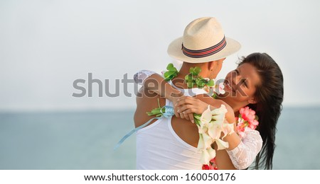 Groom with bride wearing lei - stock photo