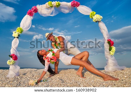 Groom with bride wearing lei, dancing under archway on beach - stock photo
