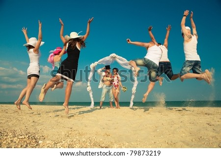 Groom with bride wearing lei, standing under archway on beach and  their friends jumping for joy - stock photo