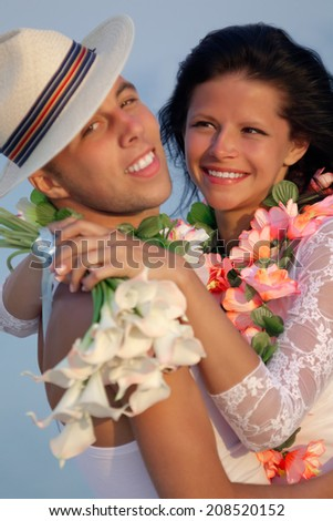 Groom with bride wearing lei, standing under archway on beach (Focus is on bride) - stock photo
