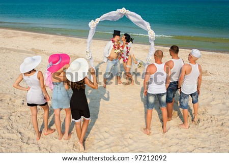 Groom with bride wearing lei, standing under archway on beach with  their friends - stock photo