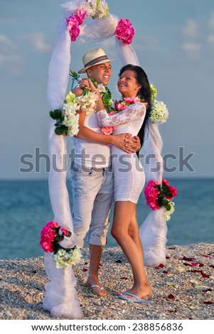 Groom with bride wearing lei  under archway on beach - stock photo