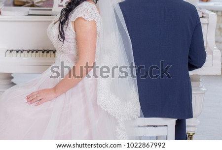 groom with the bride near the piano