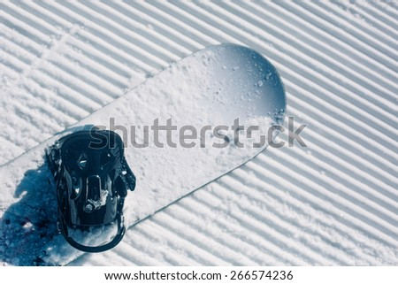 groomed empty ski piste background with snowboard - stock photo