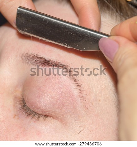 grooming eyebrows in a beauty salon - stock photo