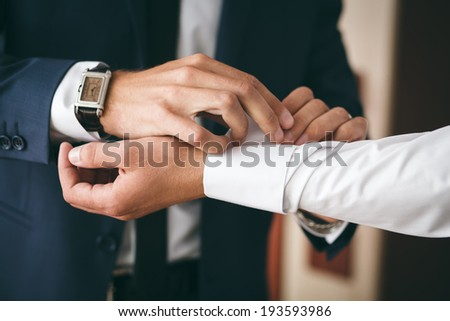 Groomsman helps to groom to put on cufflinks