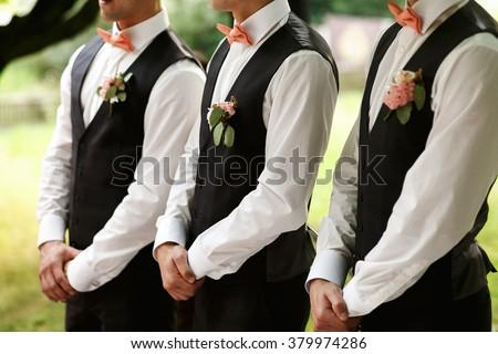 Groomsmen standing on the wedding ceremony outdoors - stock photo