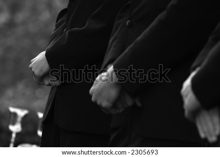 Groomsmen waiting with hands crossed - stock photo