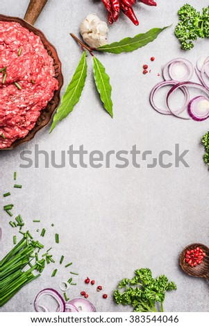 Ground beef with fresh herbs and spices on gray concrete texture background, top view, place for text, frame. Meat food - stock photo