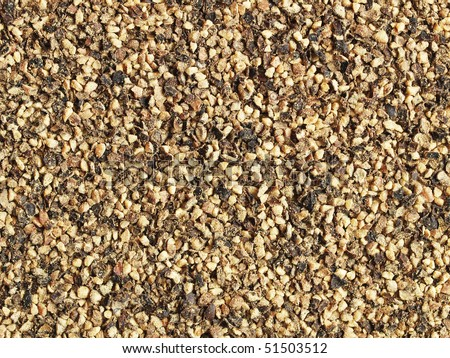 Ground black pepper (coarse) - close-up; can be used as a background - stock photo