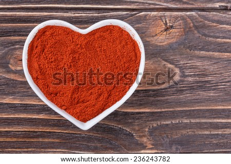 ground chili pepper in a bowl in the form of heart on a wooden background - stock photo