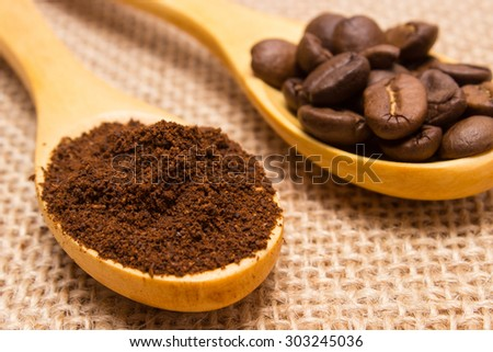 Ground coffee and coffee beans on wooden spoon lying on jute canvas, coffee grains - stock photo