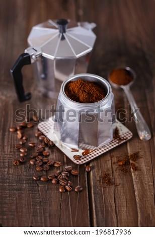 Ground coffee, coffee beans and Moka Pot coffee maker over rustic wooden background. Selective focus, shallow DoF - stock photo