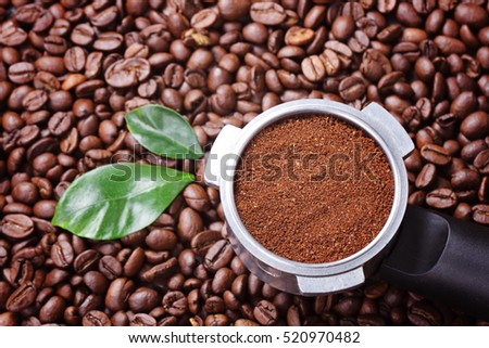 Ground coffee in filter with coffee beans