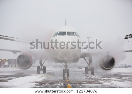 Ground crew of provides de-icing. They are spraying the aircraft, which prevents the occurrence of frost. Prague, Czech Republic. - stock photo