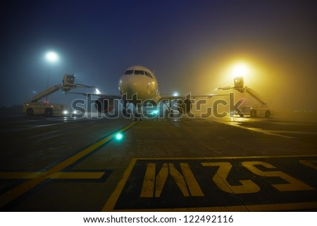 Ground crew provides de-icing. They are spraying the aircraft, which prevents the occurrence of frost. - stock photo