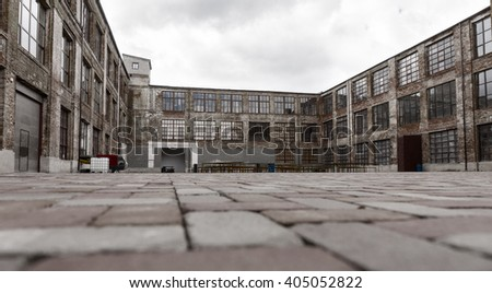 Ground level view from brick paving stones of old warehouse exterior with large windows and dock doors under gray cloudy sky - stock photo