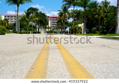 Ground level view of road in Naples Florida with building in background.