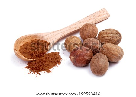 Ground nutmeg in a wooden spoon and a whole nutmeg - stock photo
