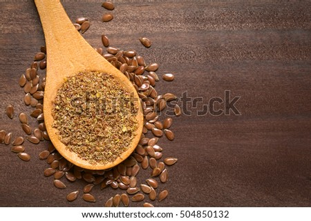 Ground or crushed brown flax seed or linseed on wooden spoon, photographed on dark wood with natural light